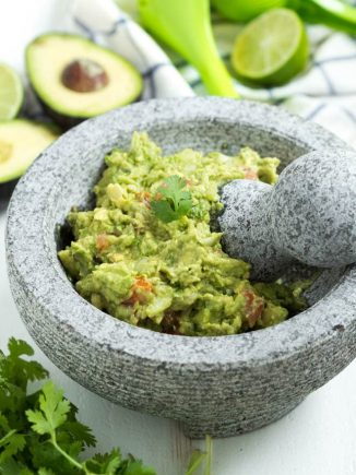 guacamole in a mortary with a spring of cilantro on top. Avocado, cilantro and lemon on the table next to the bowl.
