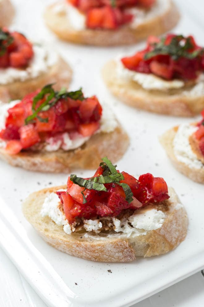 six slices of strawberry bruschetta sitting on a white plate