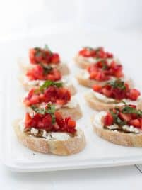 eight slices of strawberry bruschetta sitting on a white plate on a white table