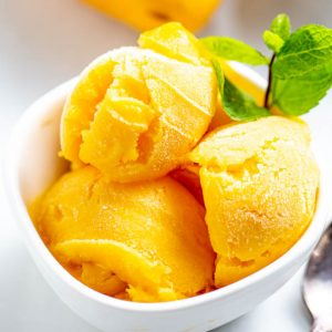 Three scoops of mango sorbet in a white bowl.