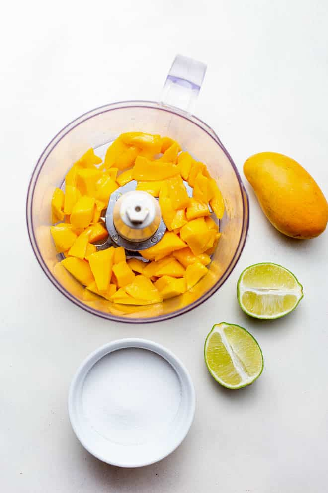 Mango in a food processor with a bowl of sugar and limes off to the side.