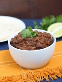 A bowl of Mexican black beans sitting on a table with a blue tablecloth and yellow napkin.