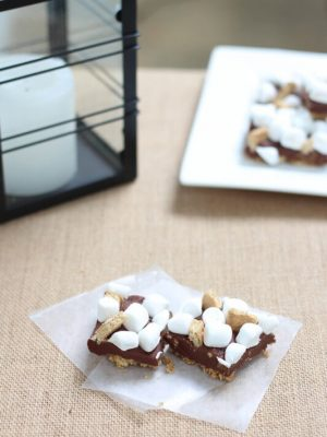Two S'mores Bars sitting on a table with a plate full of bars off to the side.