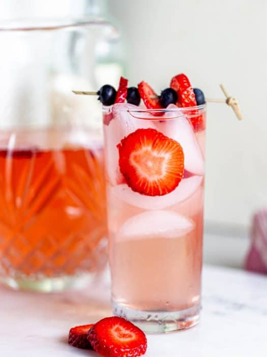 A large glass of strawberry sangria with fresh strawberry slices.