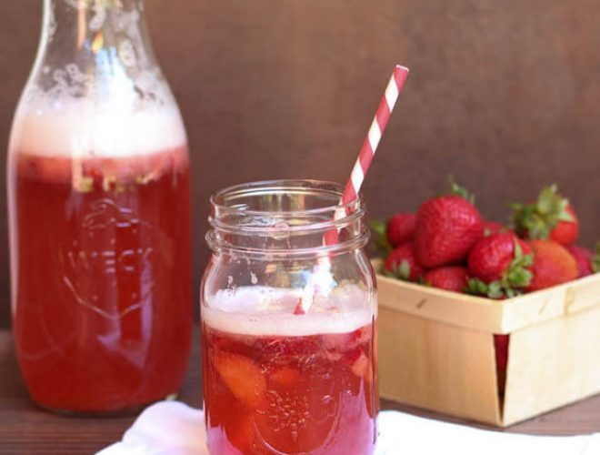 A glass of strawberry sangria sitting on a table with a pitcher in the background.