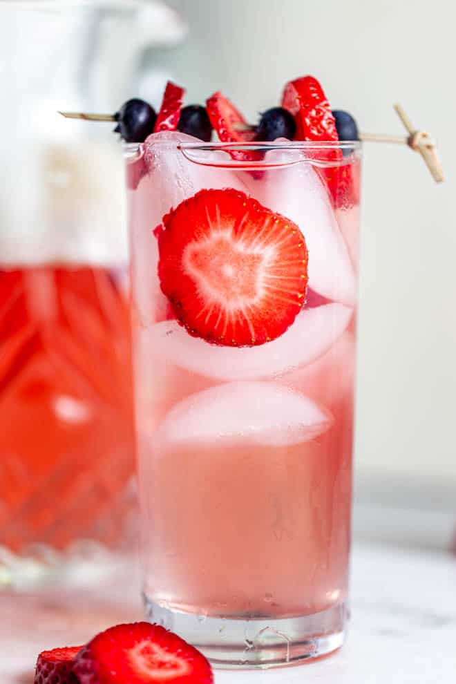 A large glass of strawberry sangria with ice and strawberry slices.