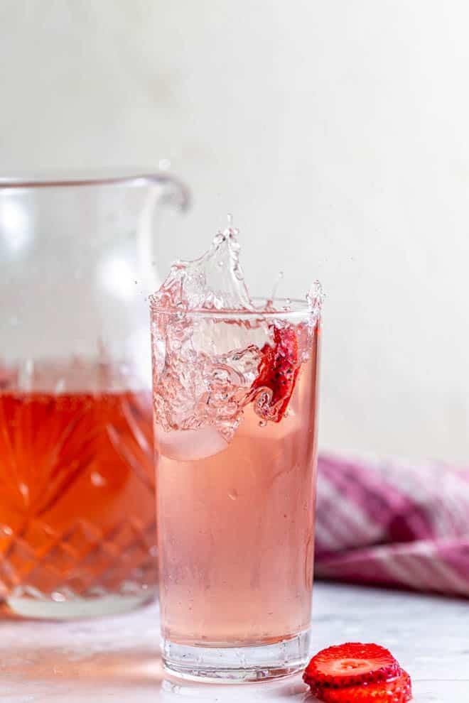 A strawberry drops into a glass of homemade strawberry sangria.