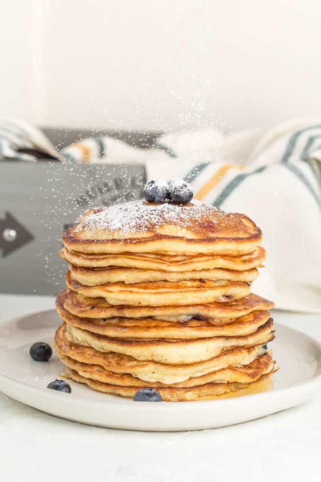 A large stack of blueberry pancakes witting on a white plate with a stripe napkin in the background.
