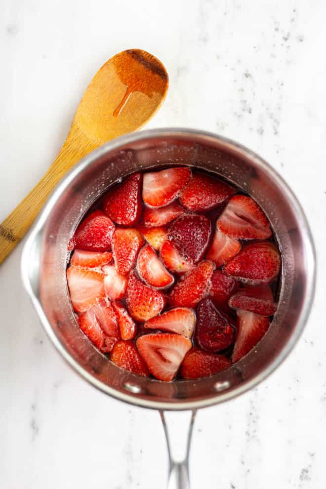 A bowl of strawberries simmering on the stove.