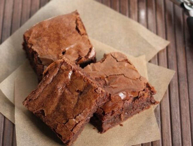 Three brownies sitting on brown parchment paper on a wood table.