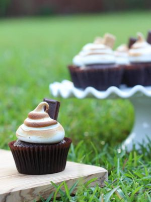 One S'mores cupcake sitting on a wood cutting board on the grass with a cake plate full of cupcakes in the background.