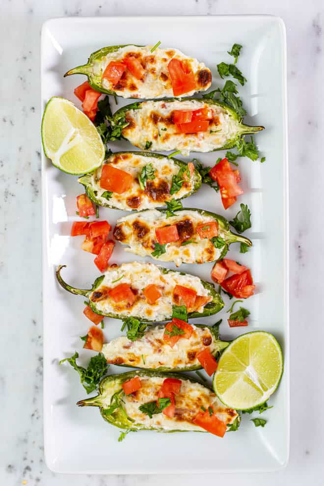 Seven grilled stuffed jalapeno peppers on a plate.