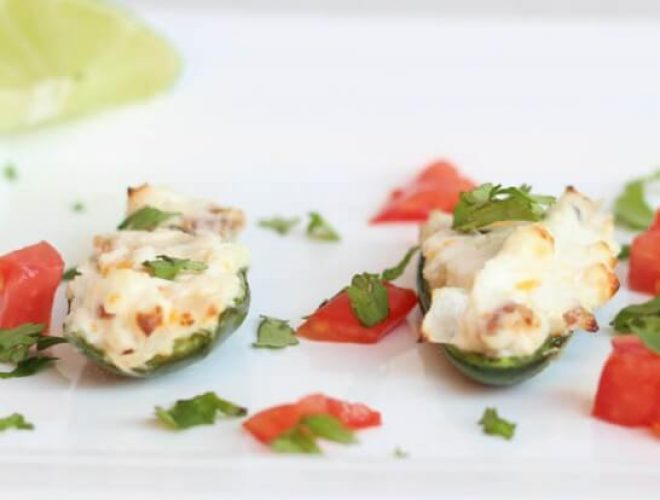 Three stuffed jalapenos sitting on a white plate with cilantro garnish and a lime off to the side.