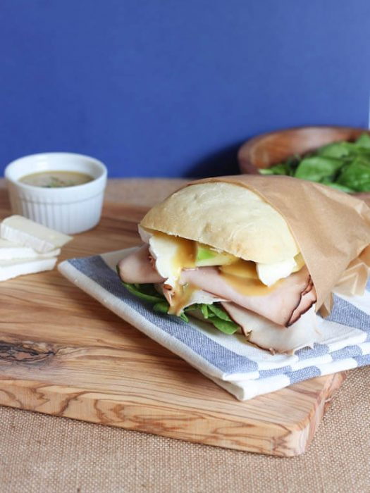 A Turkey Brie Sandwich wrapped in brown paper sitting on a blue stripe napkin on a wood cutting board.