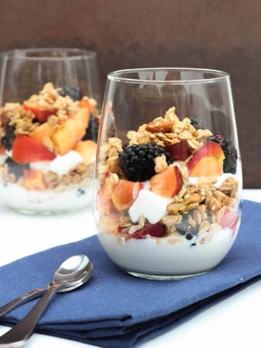 Blackberry and nectarine yogurt parfait with yogurt, granola and fruit in a glass sitting on a blue napkin.