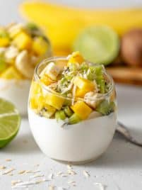 clear glass jar filled with greek yogurt with mango, kiwi, banana and pineapple chunks piled on top