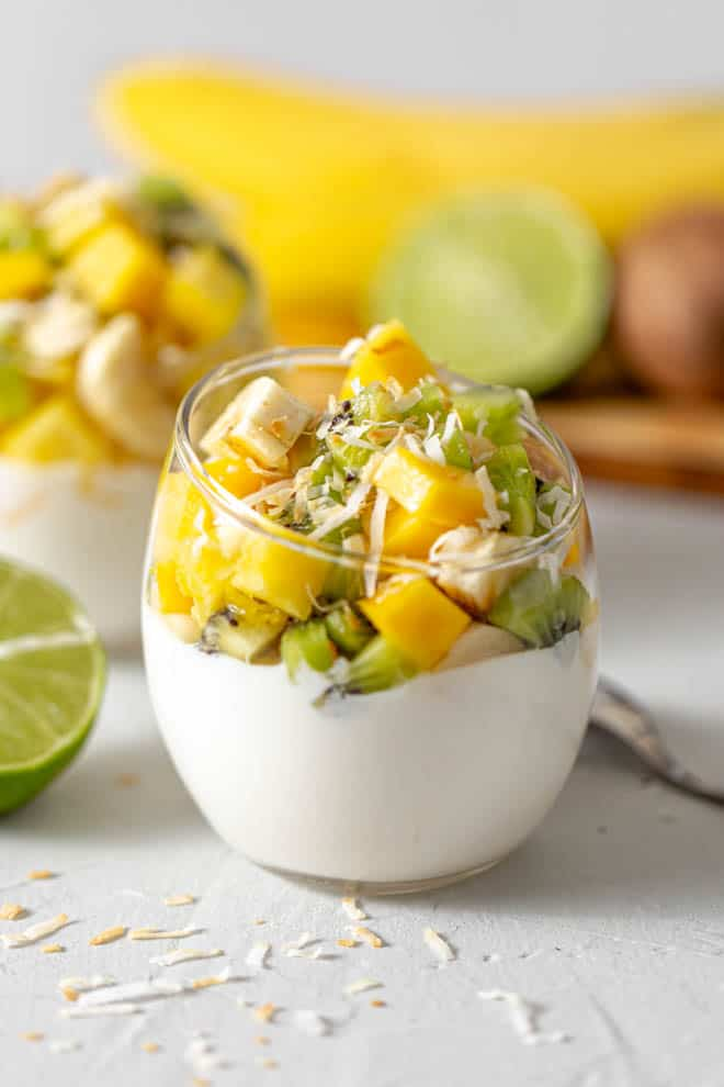 clear glass jar filled with greek yogurt with mango, kiwi, banana and pineapple chunks piled on top