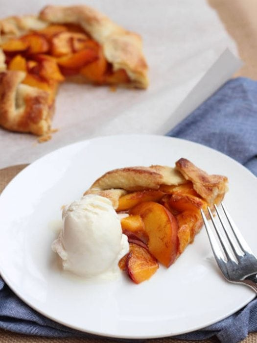 A slice of peach tart sitting on a white plate with one scoop of vanilla ice cream and a fork.