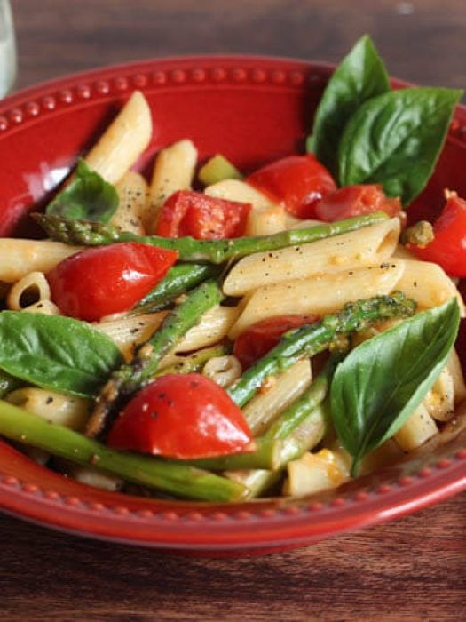 Penne pasta with asparagus and tomatoes in a red bowl on a wooden table.