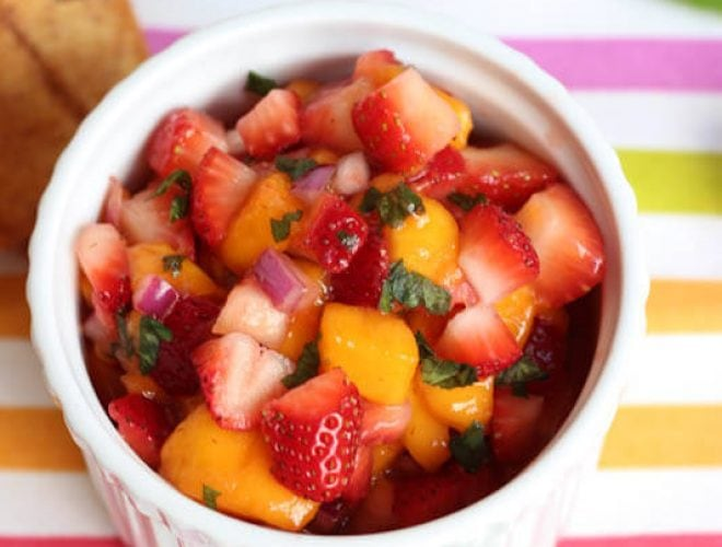 Strawberry and mango salsa in a white bowl on a colorful striped napkin with cinnamon chips for dipping.