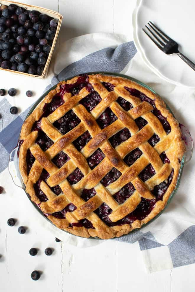 a baked blueberry pie sitting on a white table with a basket of blueberries off to the side