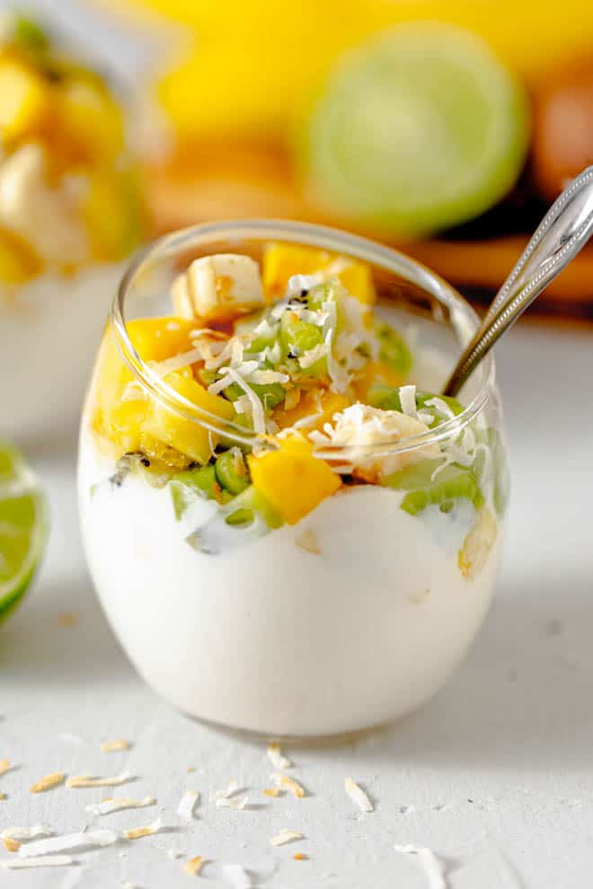 clear glass bowl with greek yogurt and mango, banana and kiwi on top with toasted coconut.