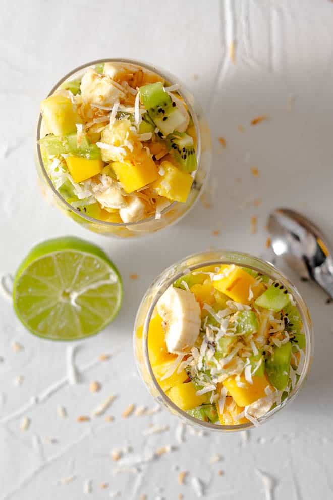 two glasses sitting on a white table with mango, pineapple, kiwi and banana chunks plus toasted coconut flakes. A spoon and lime sitting on the side of the glasses.