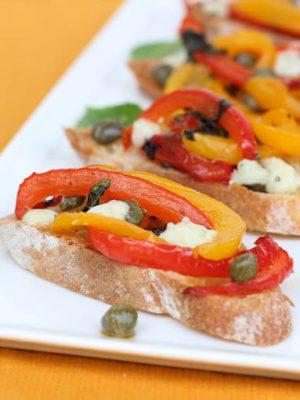 Brushetta with peppers sitting on a white plate on a yellow table cloth.