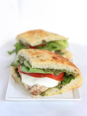 Two grilled chicken pesto sandwiches sitting on a white plate.