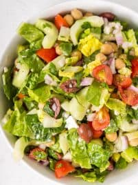 A white bowl filled with chopped Mediterranean salad including chicken peas, lettuce, tomatoes, olives and cucumbers.