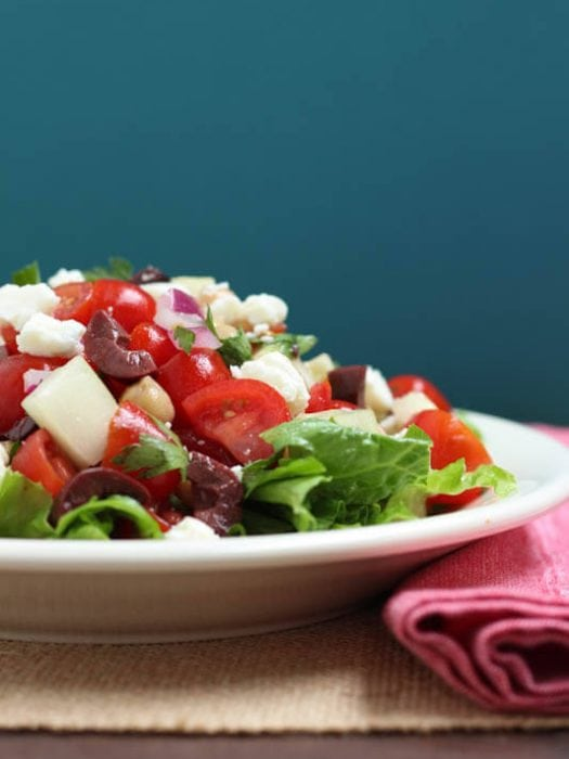 A chopped mediterranean salad sitting on a white plate on a burlap placemat next to a red napkin.