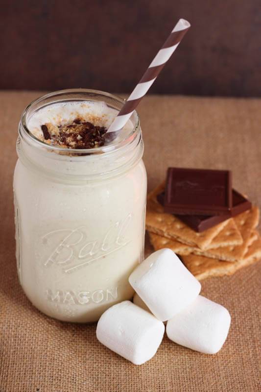 One S'mores milkshake sitting on a brown backdrop with a stack of graham crackers, chocolate and marshmallows.