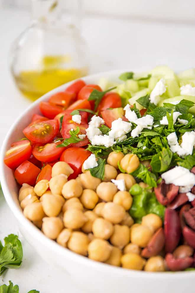 A bowl sitting on a white table filled with chickpeas, tomatoes, cucumbers, parsley, olives and feta with a salad dressing bottle on the side.