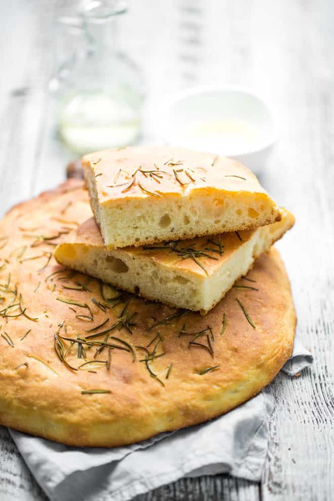 A loaf of rosemary focaccia bread with cut pieces of bread on top.