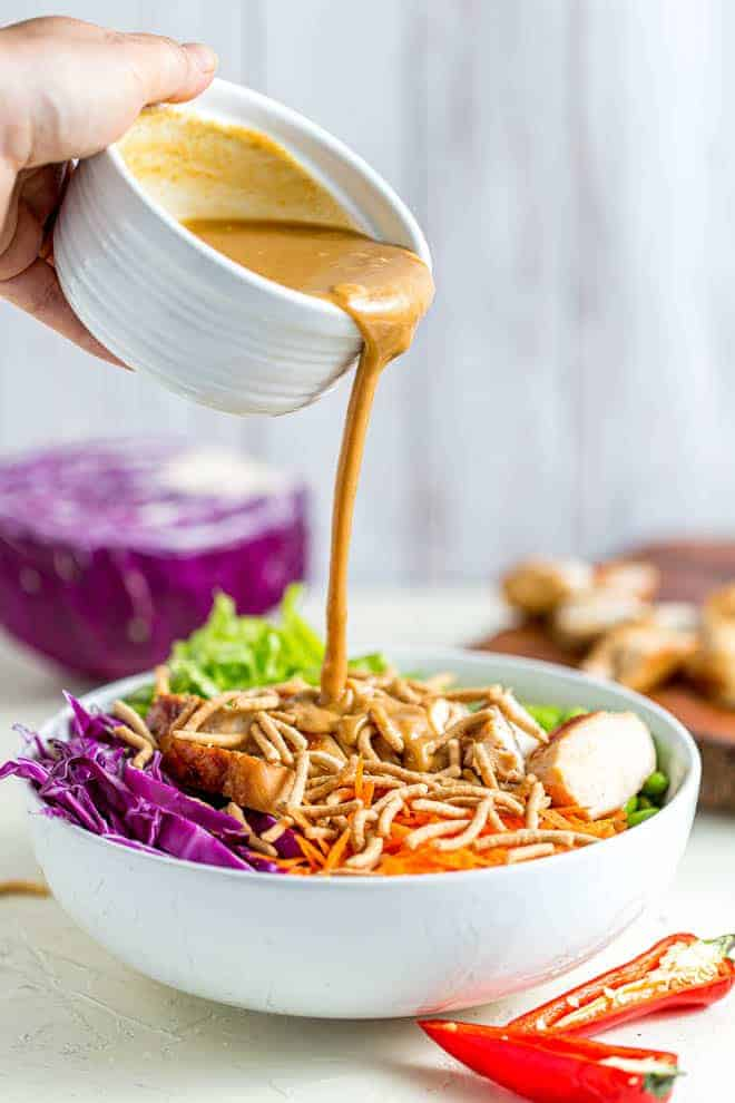 Pouring peanut sauce into a bowl of thai chicken salad.