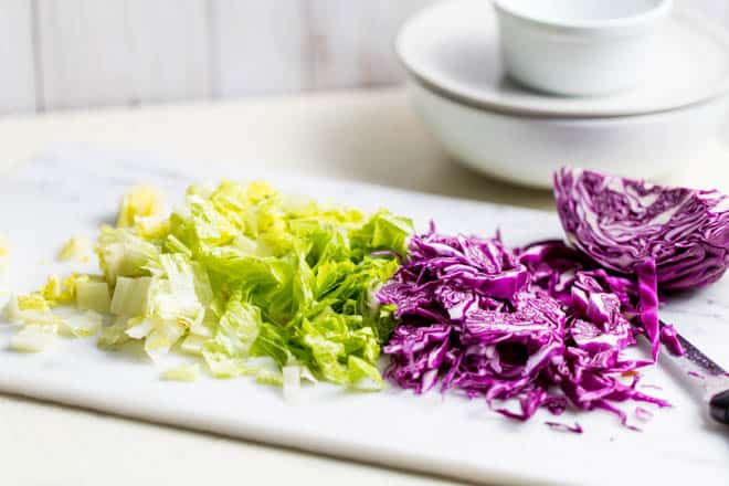 Chopped lettuce and cabbage on a white cutting board.