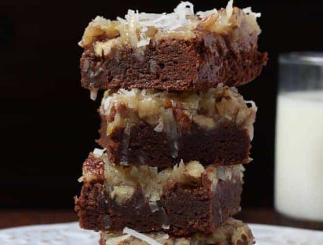 Four coconut pecan brownies sitting in a stack on a white plate on a black background.