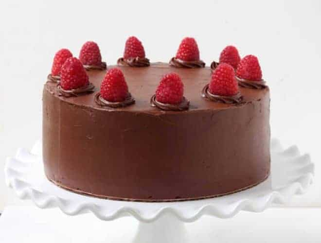Chocolate Cake with fresh raspberries on top sitting on a white cake platter.