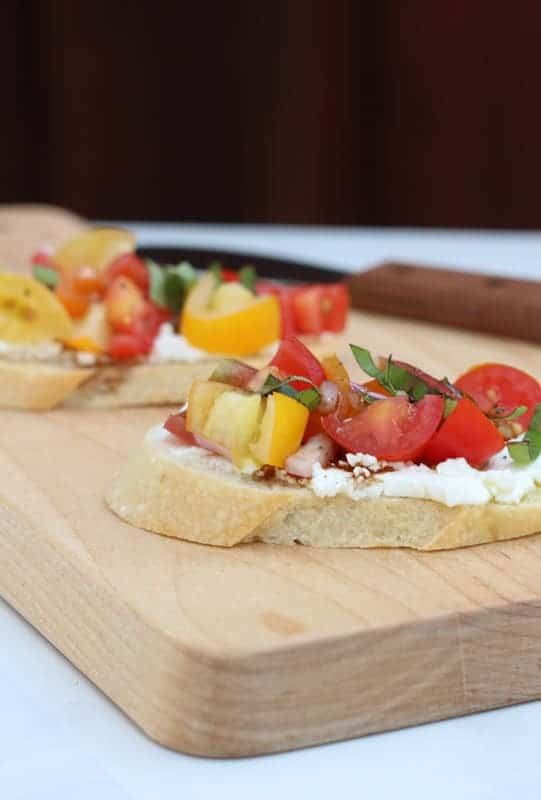 Two slices of tomato bruschetta sitting on a wooden cutting board on a white table. A small knife is on the cutting board.