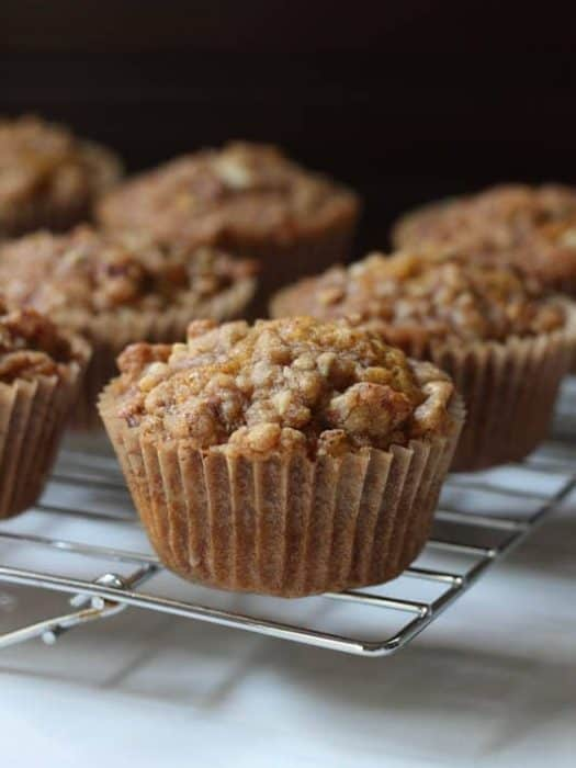 Pumpkin muffins sitting on a cooling rack on a white table.