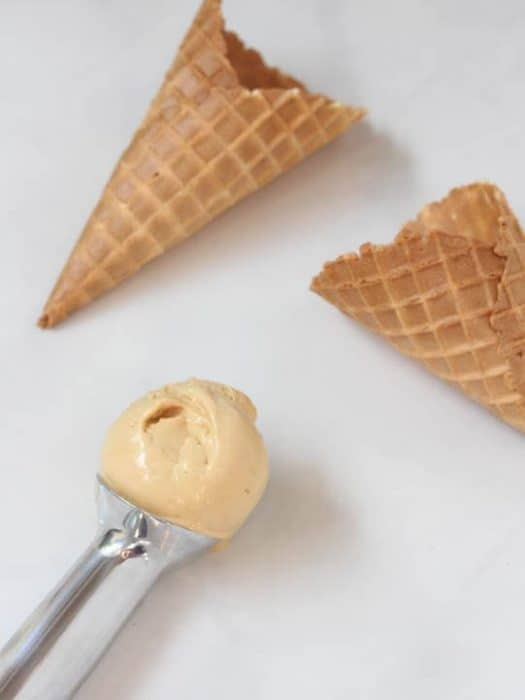 One scoop of salted caramel ice cream sits in an ice cream scoop next to two sugar cones.