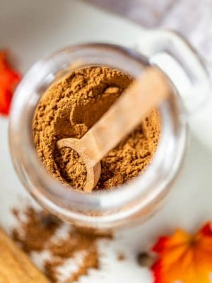 scooping out pumpkin pie spice from a jar