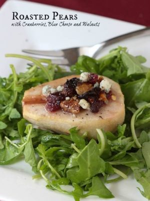One pear sliced in half filled with cranberries, blue cheese and dressing over a bed of arugula on a white plate with a red napkin.