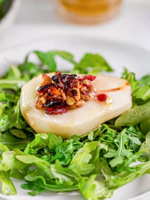 Roasted pear with blue cheese, cranberries and walnuts sitting on a bed of arugula on a plate.