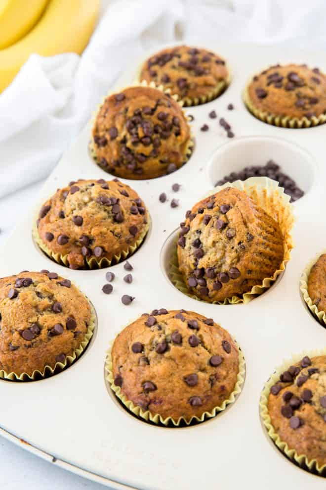 a muffin pan filled with baked banana chocolate chip muffins