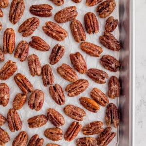 candied pecans on a piece of white parchment paper on a baking sheet