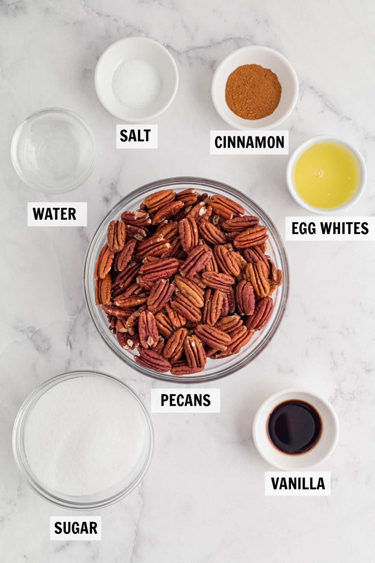 all of the ingredients for the candied pecans on a white countertop