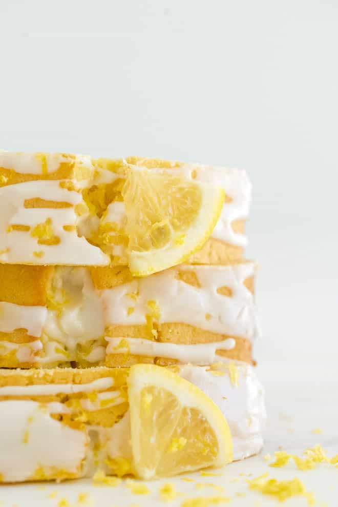Three slices of lemon loaf cake stacked on top of each other on a white background