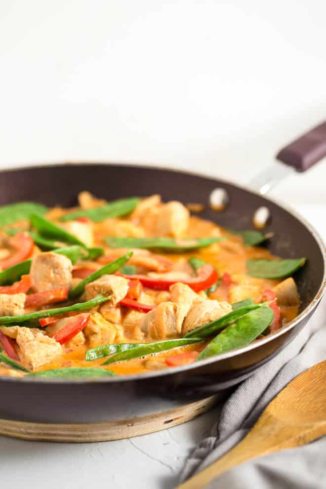 A saute pan filled with coconut sauce, fresh vegetables and chicken.