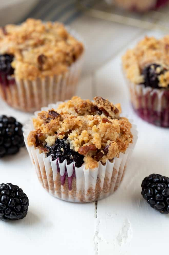 three blackberry muffins sitting on a white table next to a few fresh blackberries